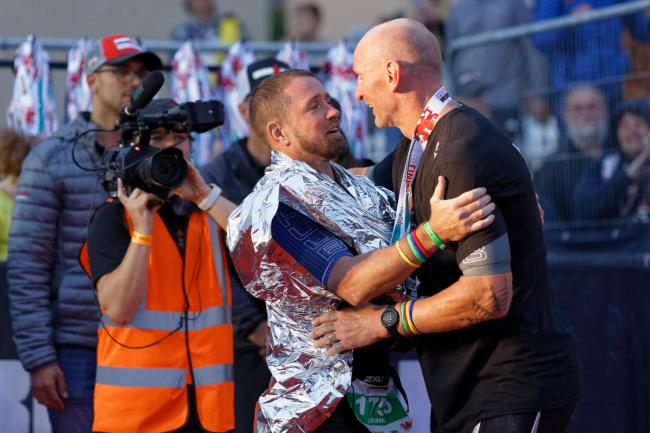 Shane Williams and Gareth Thomas embrace at the finish line.