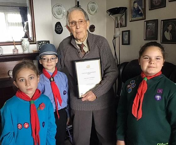 Scout Owain Williams, cub Imogen Thomas and beaver Rose Evans present Jac Williams with his long service certificate. PICTURE: Johnny Morris