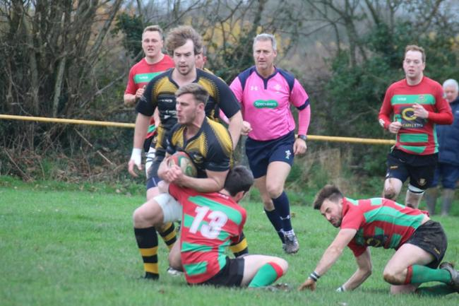 Llangwm centre Josh Hicks is tackled in midfield. PICTURE: Western Telegraph.