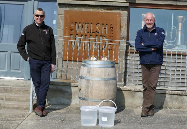 John Williams lifeboat operations manager for St Davids and Aberystwyth deputy launch authority, Paul Williams, collect their initial hand sanitiser donations from the Tan y Groes distillery.