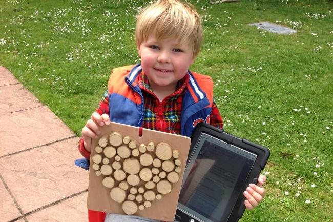 Alfie William Hughes is pictured with his home-made wooden heart and his message for the Welsh education minister