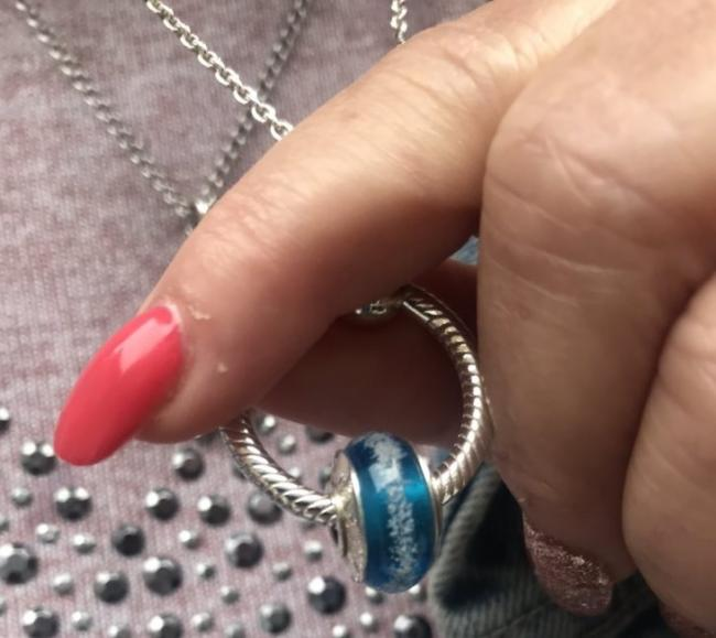 The charm on the bracelet is white, of a similar type to the blue one pictured
