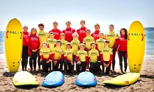 RNLI lifeguards Nicky Palmer, Michael Vincent, Kylie Jones, Owen Evans, Sam Willmott and Olivia Draper with the Kiln Park youngsters. Pic: Owen Howells/RNLI.