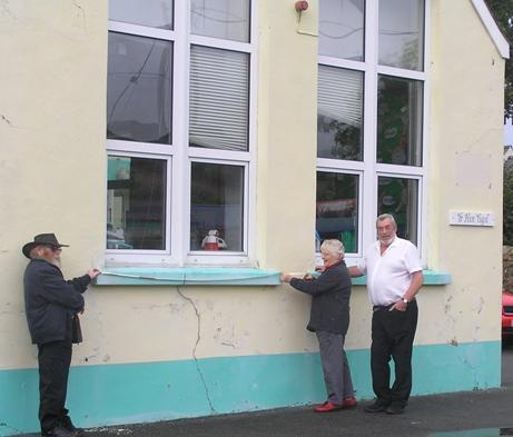 Yr Hen Ysgol management committee members Pete & Sheila Duffill help High Sheriff volunteer Brian Murray to measure their community hall frontage.