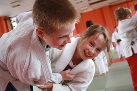 Children enjoying judo, one of the man