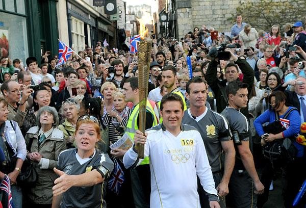 Western Telegraph: Luke Young carries the Olympic torch along Shamble