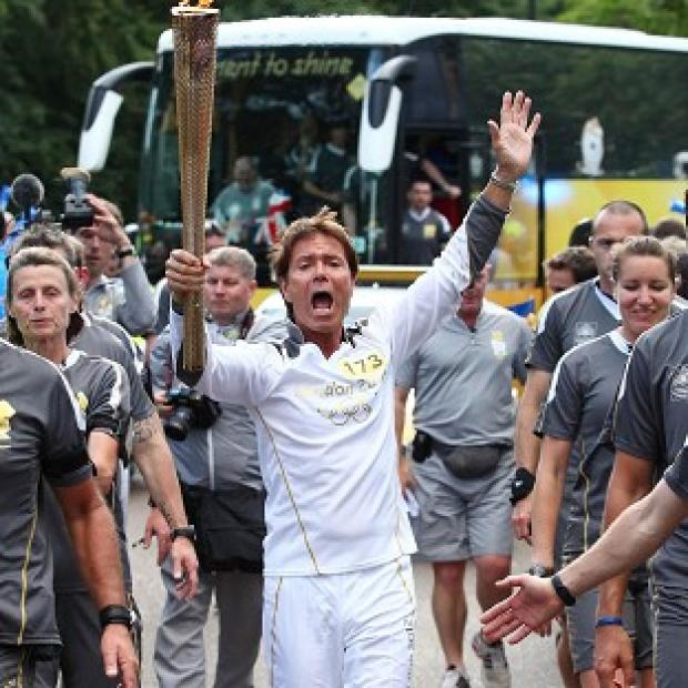 Sir Cliff Richard carrying the Olympic Flame on the Torch Relay leg through Birmingham