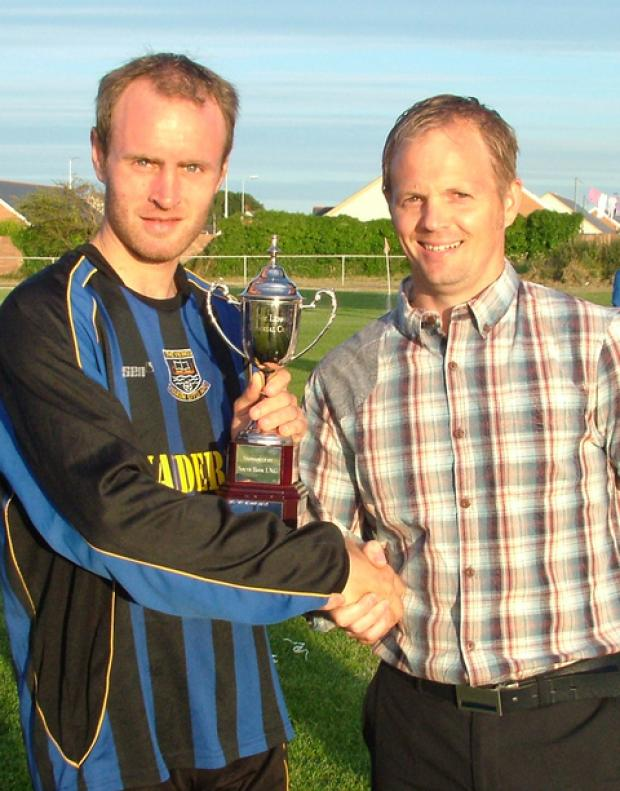 Hakin skipper Mathias received the trophy from organiser Stuart MacDonald..