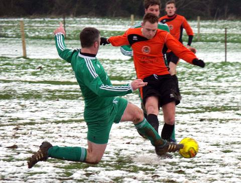 Western Telegraph: Joe John shoots and scores despite pressure from Solva's Richie Davies.
