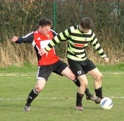 Goodwick centre back Anthony Couzens puts in a strong tackle on Neyland's Craig Lucas.