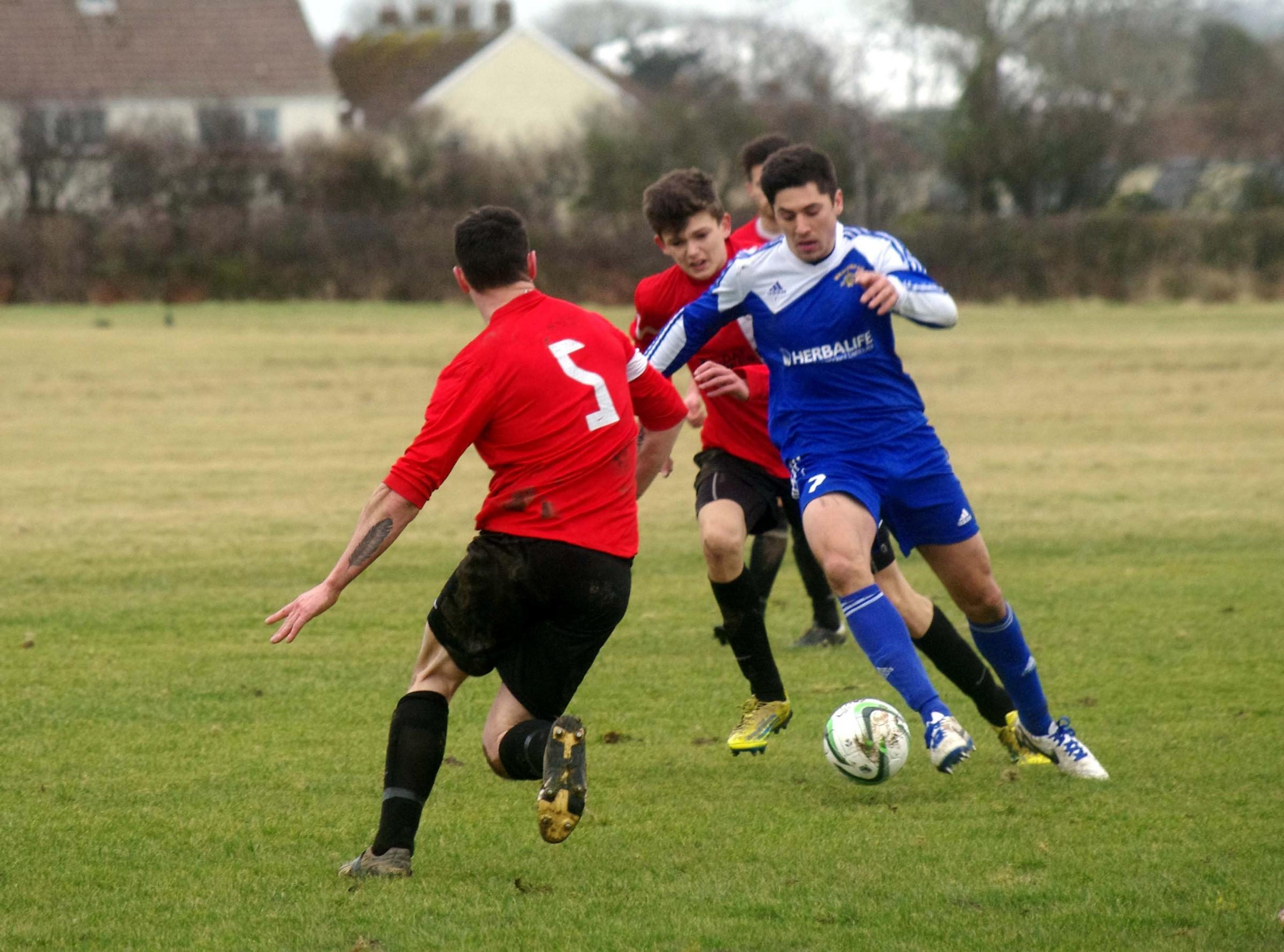 CUP CLASH: Matthew D'Ivry takes on Clarbeston Road defenders in Merlins Bridge's comfortable passage into the semis. PICTURE: Western Telegraph. (4209897)