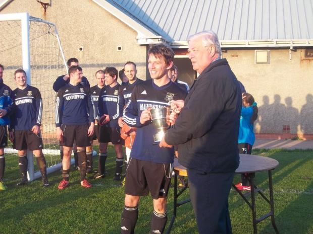Western Telegraph: WELL LED: Hakin skipper Ewan Findlay receives the trophy from Dave Olyott, chairman of the Pembrokeshire Football League.