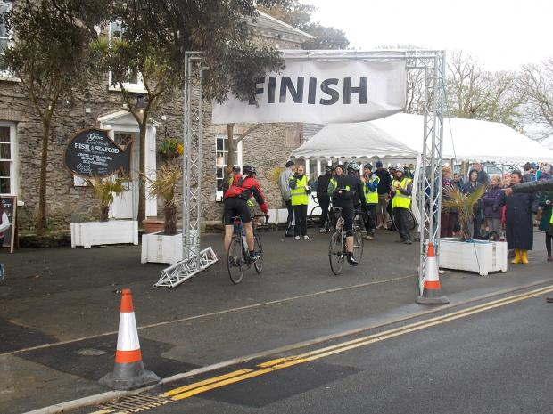 DONE AND DUSTED: Two cyclists complete the 100-mile route.