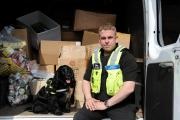 GOOD HAUL: Stuart Phillips and sniffer dog Phoebe with the items of illegal tobacco they found.