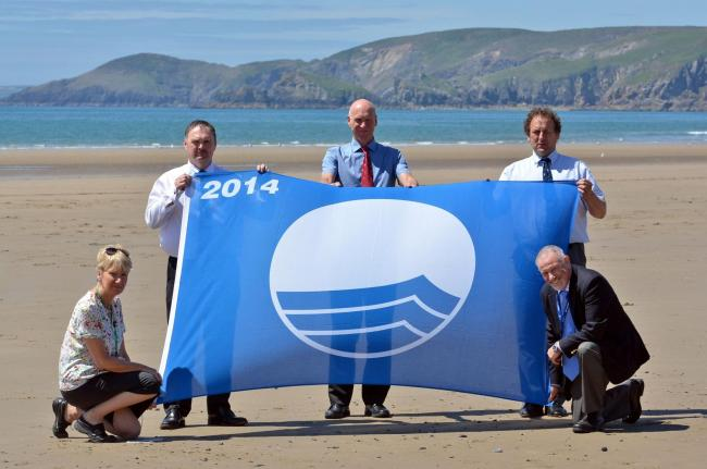 FLYING THE FLAG: Pictured with one of Pembrokeshire's Blue Flags are the county council's director of adult care and leisure, Pam Marsden; cabinet member for environmental and regulatory services, Councillor Huw George; leisure services manager, C