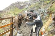National Park Authority Ranger Ian Meopham, Shane Thomas and Patrick Maher pour the last of the ten tons of concrete to complete the job at Caerfai.