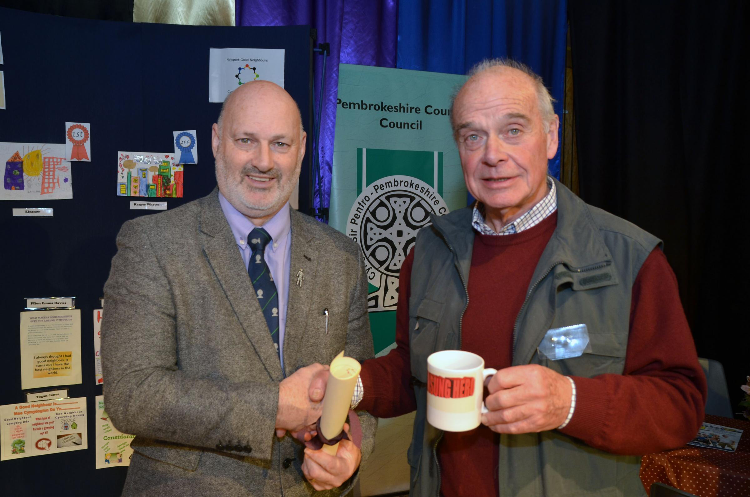 Reg Atkins (right) receives his award from Councillor Mike James.