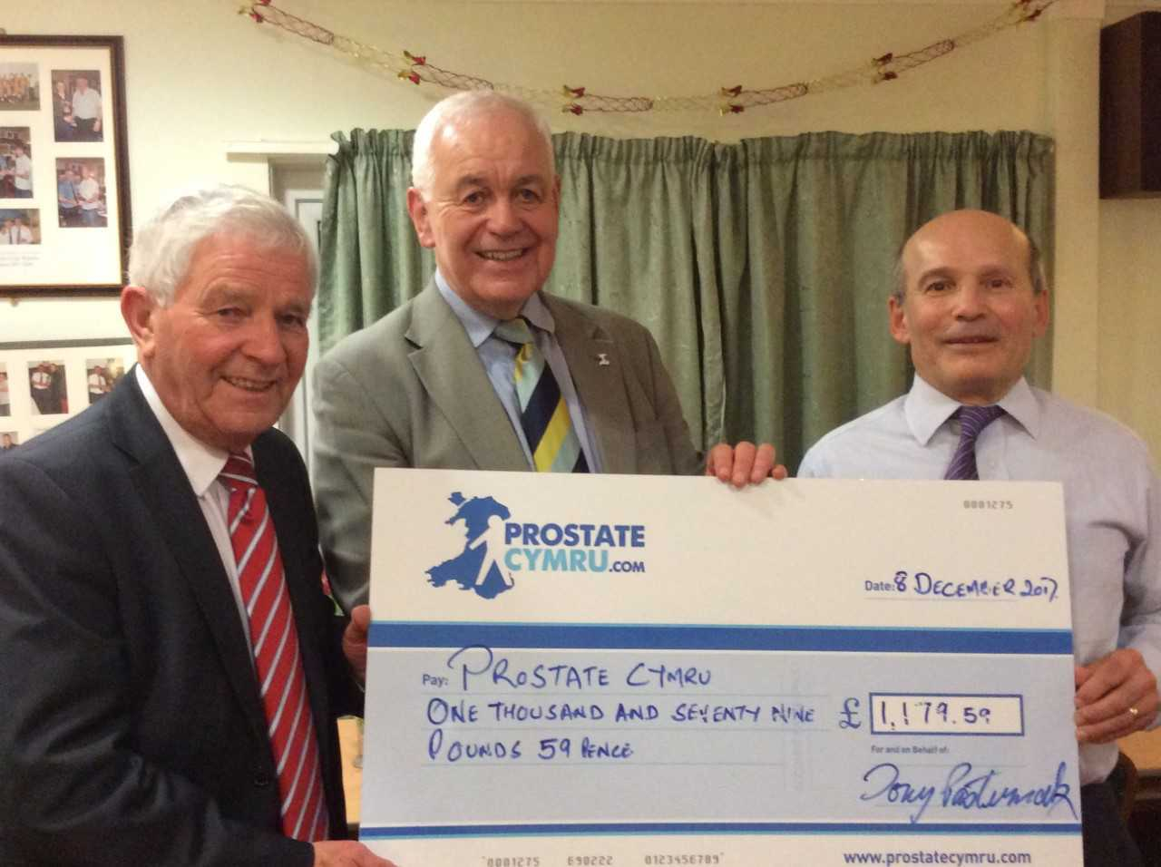 Pictured is Glamorgan and England batting legend Alan Jones, receiving the cheque from Tony Pasternak on behalf of Prostate Cymru. Also pictured is John Daniels who is a trustee of the charity.
