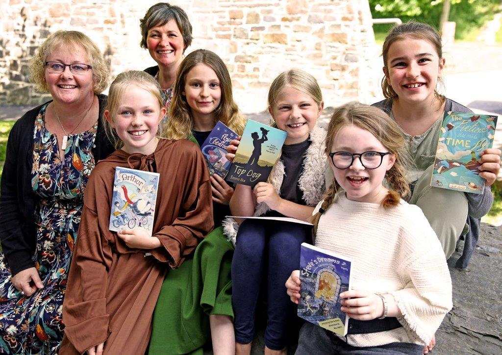Saundersfoot CP School's successful BookSlam team of Evie, Anya, Ada, Nel and Amelia are pictured with contest judges, Meinir Wyn Edwards and Eloise Williams..