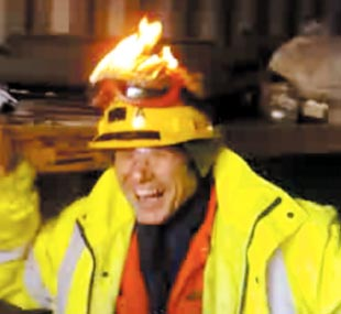 Stunt: The man posing as an LNG worker laughs uncontrollably while the goggles blaze on top of his head.