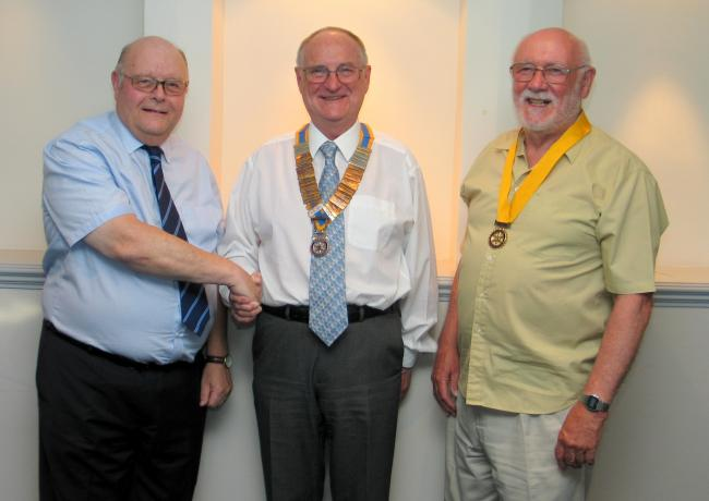 Rotary Club of Saundersfoot Immediate Past President Haydn Williams hands the chain of office to new president Neil Sefton, accompanied by new president elect Brian Jenkins.