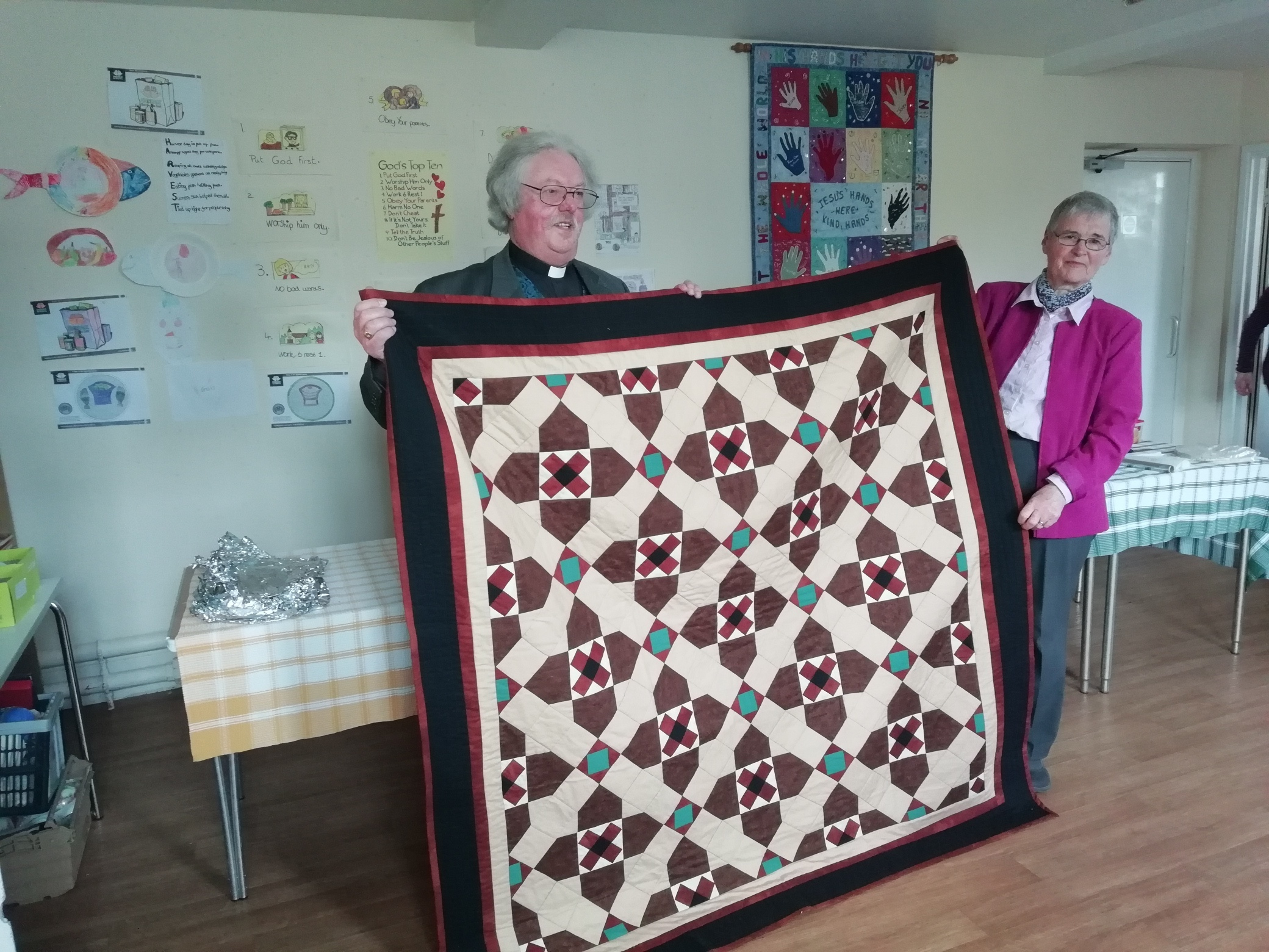 Rev Chris Gillham and Tabernacle Church Secretary, Pat Bannister with the patchwork quilt in the pattern of Tabernacle's foyer tiles, presented on the occasion of his retirement.