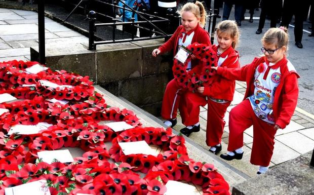 Western Telegraph: Local youngsters pay their respects in Fishguard in 2017. PICTURE: Johnny Morris